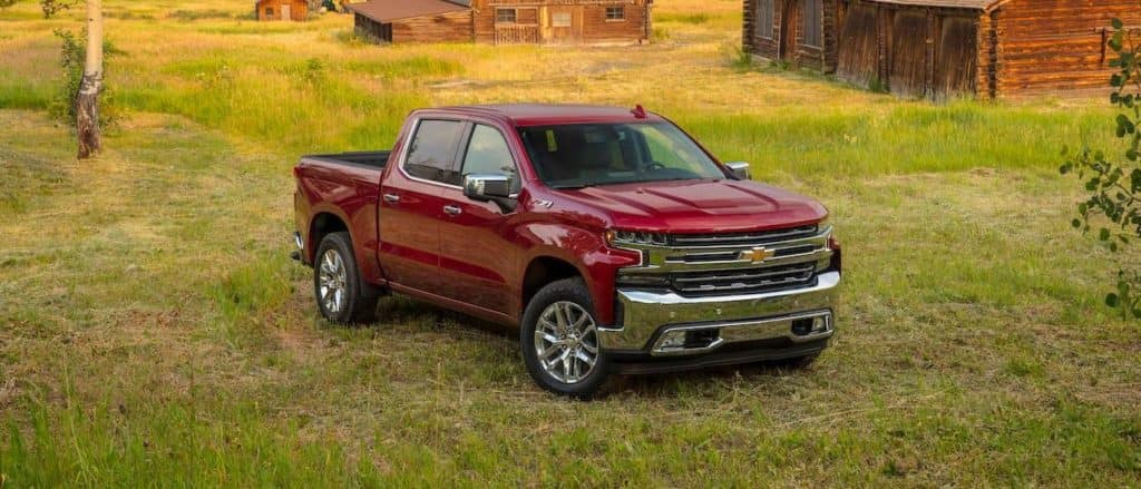 One of the most popular trucks around Corsicana, TX, a red 2020 Chevy Silverado LTZ Z71 is parked in front two wooden barns.