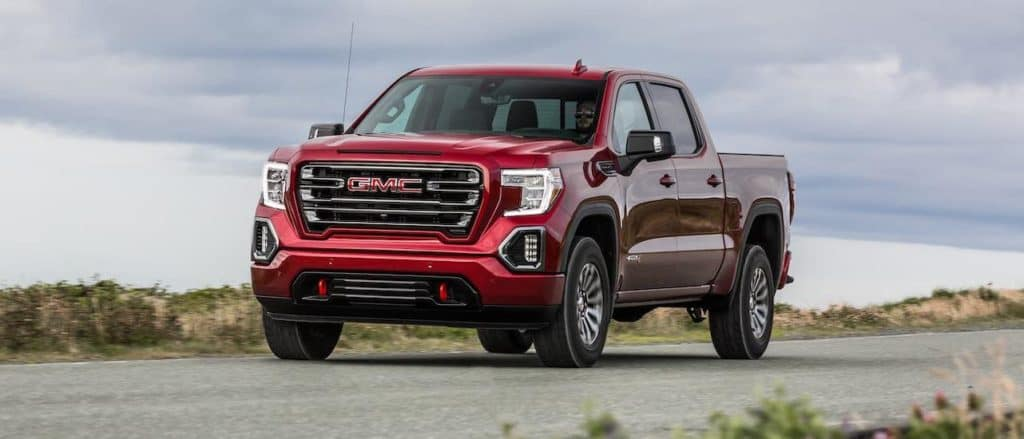 A new truck for sale in the Dallas, TX, area, a red 2020 GMC Sierra AT4, is driving on a highway.