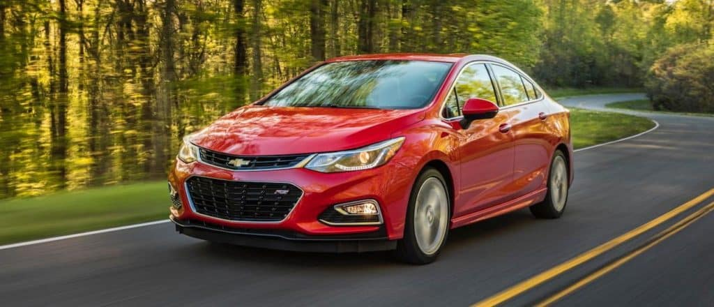 A red 2016 Chevy Cruze is driving on a tree-lined street near Navarro Country, TX, after leaving one of the used car dealerships.