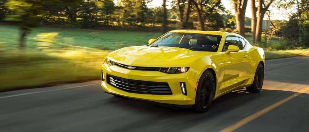 A yellow 2017 Chevy Camaro, popular when searching 'used cars for sale near me' in Corsicana, TX, is driving on a sunny road.