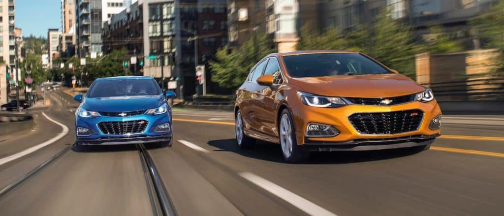 An orange 2017 Chevy Cruze Hatch is driving next to a blue one on a city street.