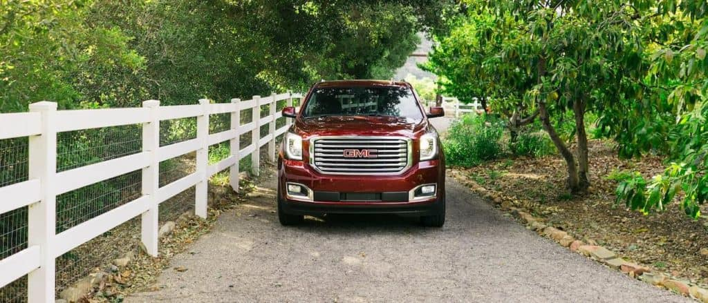 A red 2016 GMC Yukon, a popular used SUV for sale in Corsicana, TX, is driving past a white fence.