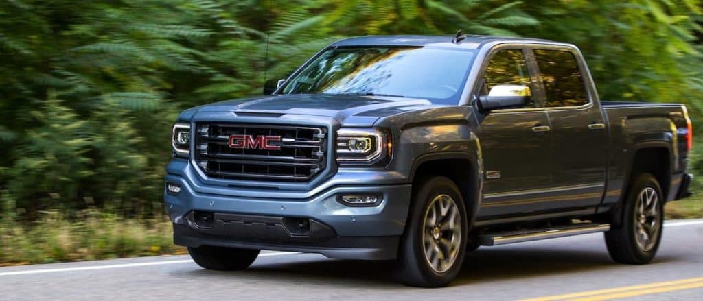 A grey 2017 GMC Sierra is driving in front of trees. The Sierra is one of the popular used trucks for sale in Corsicana, TX.