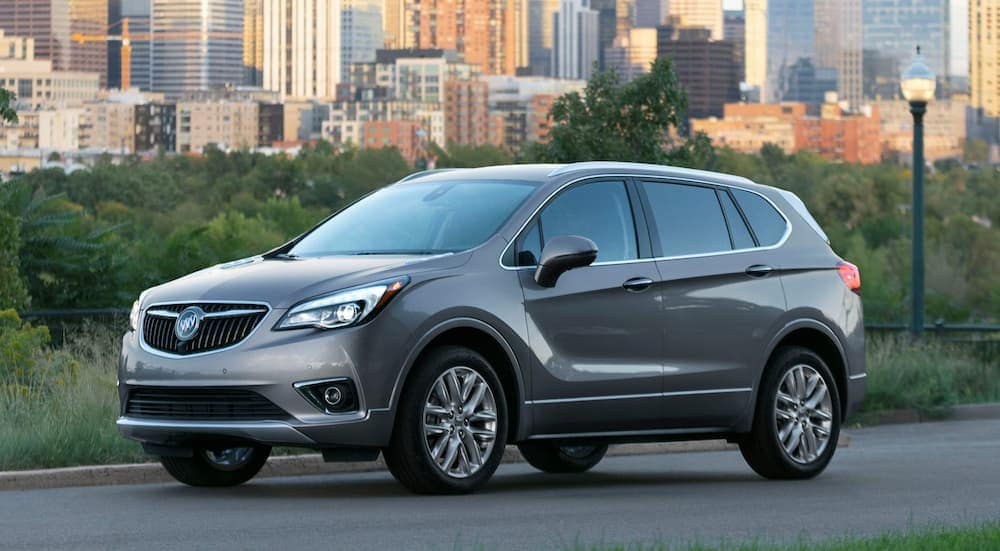 A grey 2020 Buick Envision from a Buick dealership near me is parked in front of city buildings.