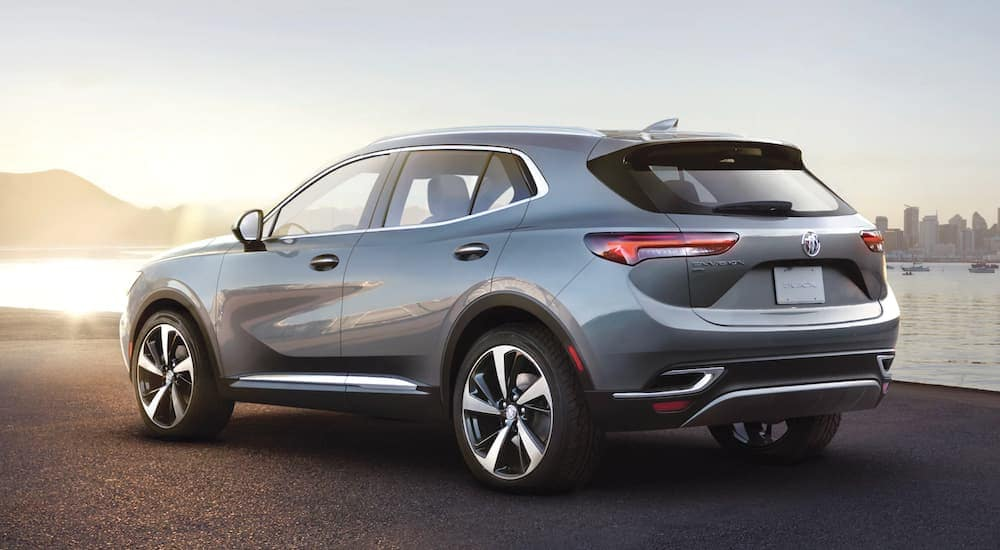 A grey 2021 Buick Envision is shown from the rear in front of a lake and sunset.