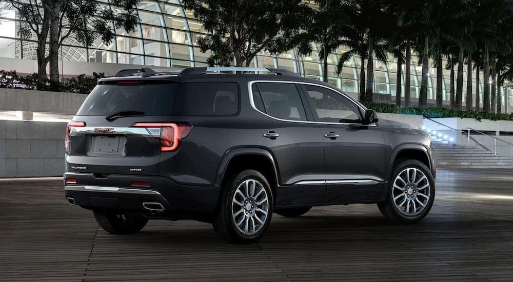 A popular GMC SUV, a black 2020 GMC Acadia, is parked in front of a glass building.