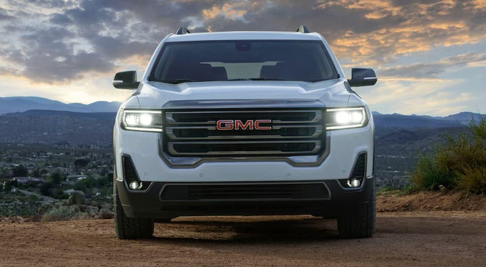 A white 2020 GMC Acadia AT4 is parked in front of mountains.