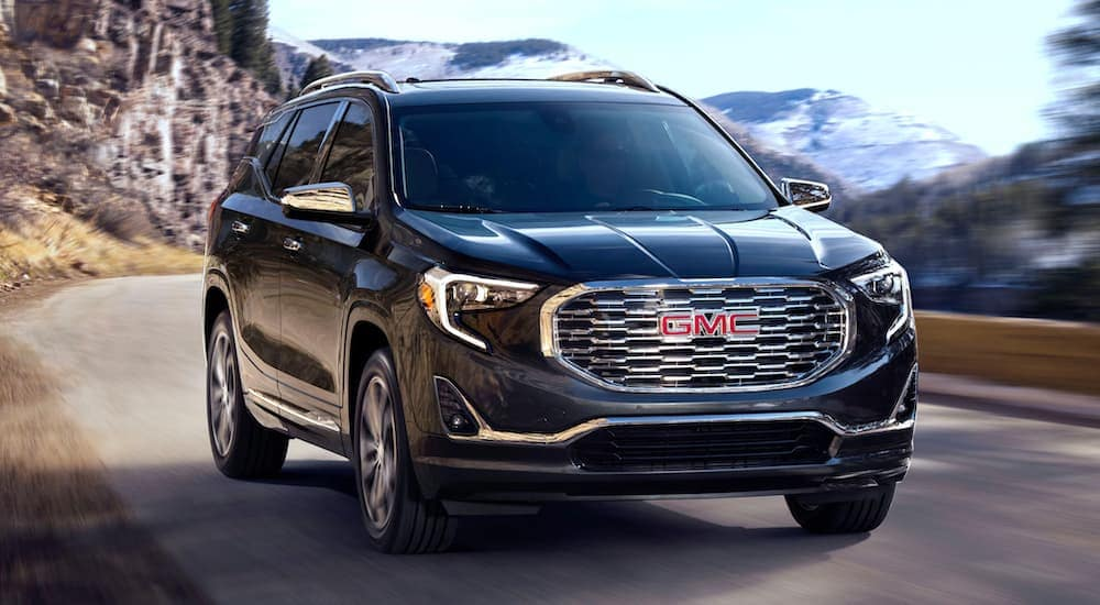 A black 2020 GMC Terrain is driving on a mountain road.