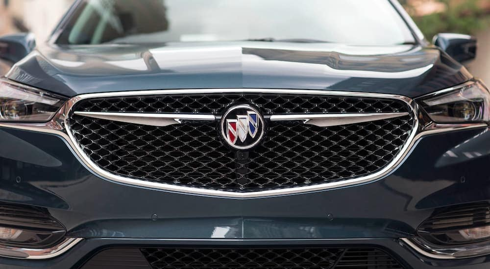 A close up is shown of the front grille and emblem on a blue 2021 Buick Enclave Avenir.