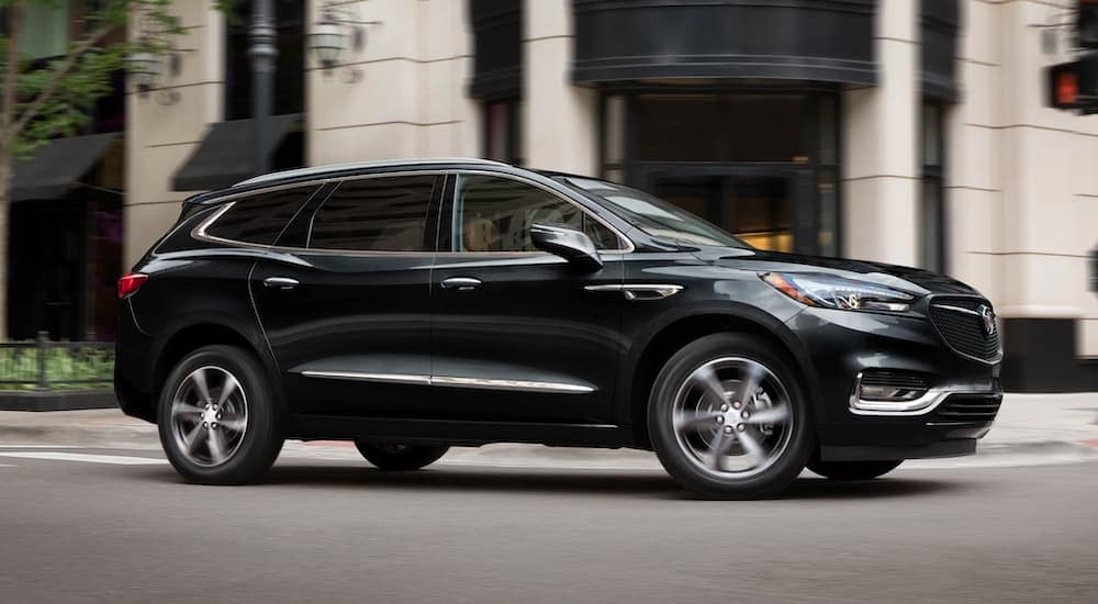 A black 2021 Buick Enclave is shown in profile driving through the city after leaving a Buick dealership near you.