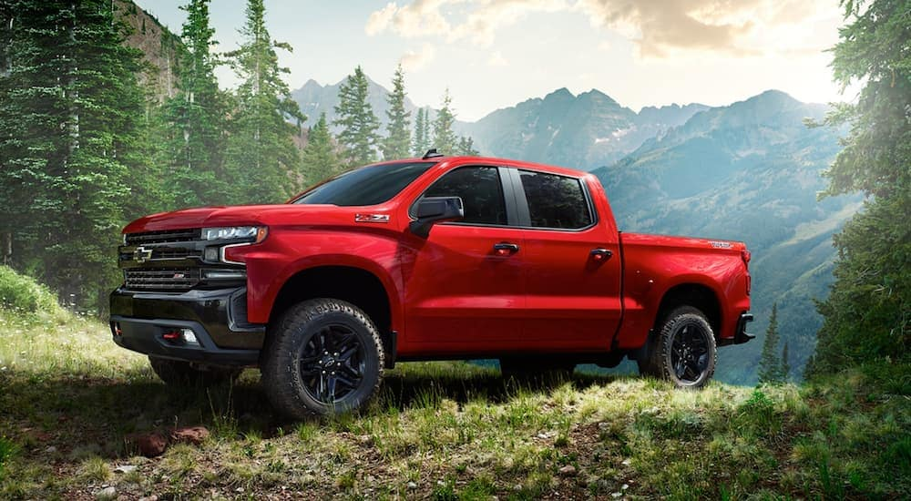 A red 2020 Chevy Silverado Trailboss is parked in the woods after leaving a Chevy dealership near you.