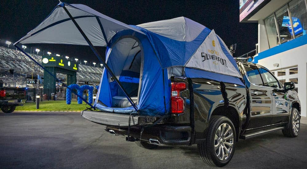 A black 2020 Chevy Silverado is shown with a tent in the bed.