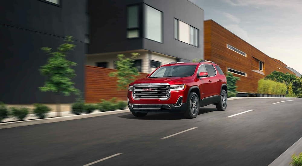 A red 2021 GMC Acadia is driving down the road past modern houses.