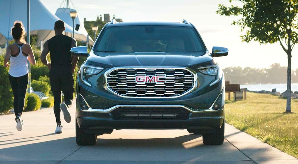 A popular GMC SUV, a dark grey 2021 GMC Terrain Denali, is shown in the park with people jogging past it.