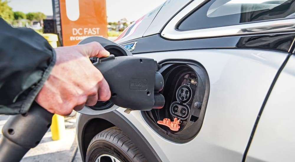 A closeup shows the charging port on a silver 2017 Chevy Bolt EV.
