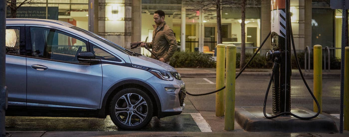 A man is about to plug in a silver 2020 Chevy Bolt EV for charging.