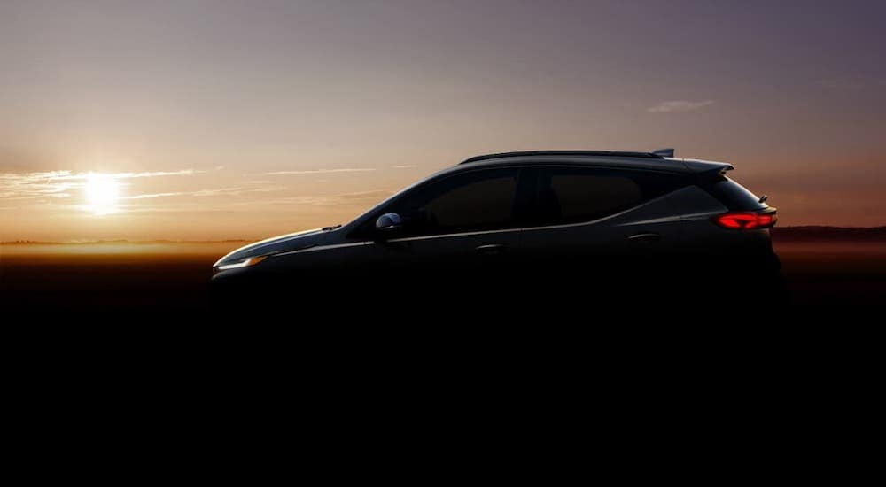 The silhouette of a 2022 Chevy Bolt EUV, a new GM EV coming to the market, is shown against a sunset.