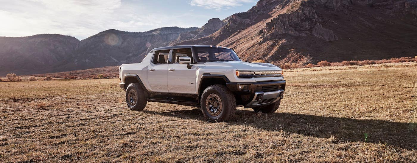 A newer GM EV in the lineup, a white 2022 GMC Hummer EV, is parked in a field in front of a mountain.