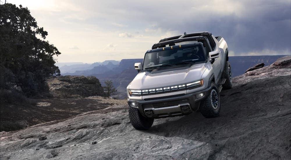 A newer GM EV, a 2022 GMC Hummer EV, is climbing over rocks.