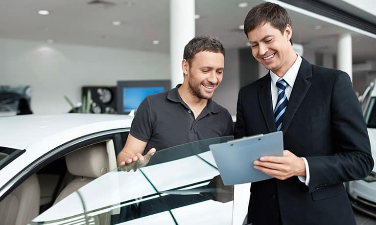 Man looking over clipboard with sales consultant
