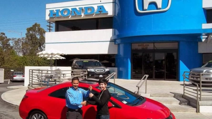 Honda salesman handing the keys over to a happy new Honda car owner