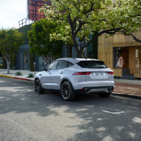 REAR VIEW OF PARKED WHITE JAGUAR E-PACE IN CITY.