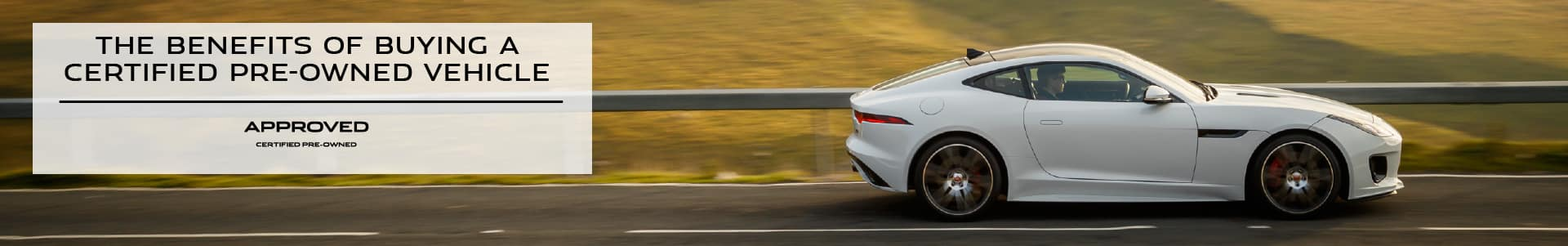 THE BENEFITS OF BUYING A CERTIFIED PRE-OWNED VEHICLE. WHITE JAGUAR F-TYPE COUPE DRIVING DOWN ROAD IN COUNTRYSIDE.