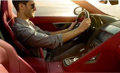 IMAGE FEATURES GENTLEMAN TEST DRIVIING A JAGUAR F-TYPE.