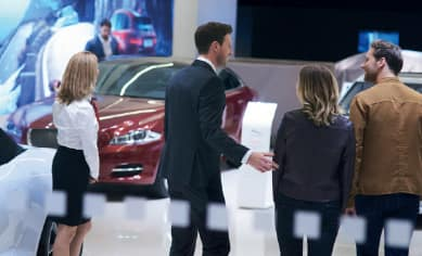 IMAGE FEATURES SALES GUIDES AND CUSTOMER IN THE JAGUAR SHOWROOM.