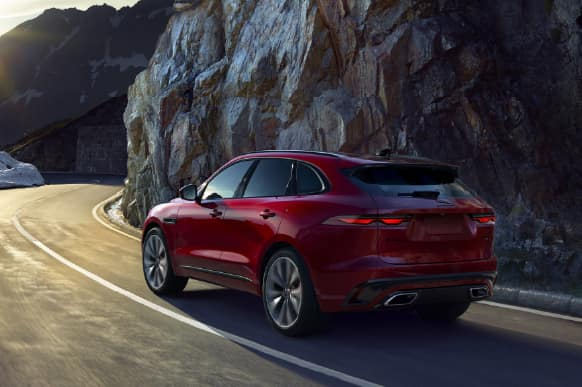 Red Jaguar F-PACE driving through mountains.