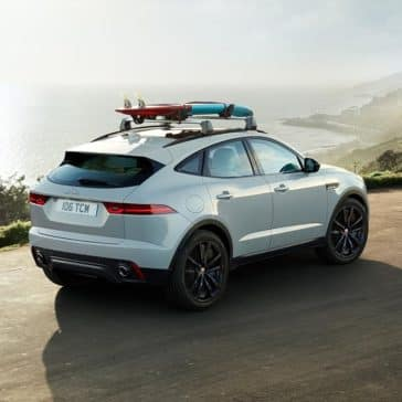 2018 Jaguar E PACE driving near beach with surf board attached on top rails