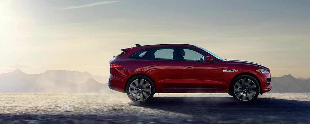 red 2019 jaguar i-pace driving on gravelly road in mountains