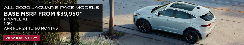 ALL 2020 JAGUAR E-PACE MODELS_BASE MSRP FROM $39,950_FINANCE AT 1.9% APR FOR 24 TO 60 MONTHS_EXPIRES MARCH 31, 2020_ WHITE JAGUAR E-PACE DRIVING DOWNTOWN PARKED NEAR A SIDEWALK AND PALM TREE