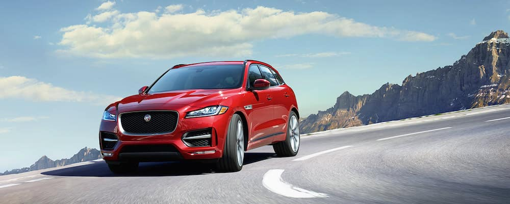 red 2019 jaguar f-pace driving on highway with mountains in background