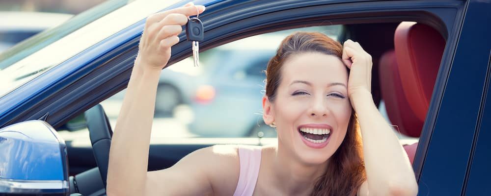 Women leaning out car window smiling and holding car keys