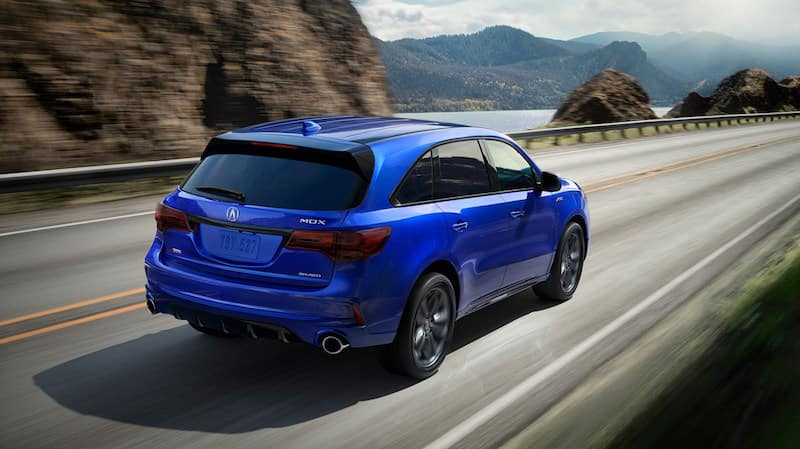 Rear view of bright blue MDX driving down a highway with a lake and brown mountains in the background