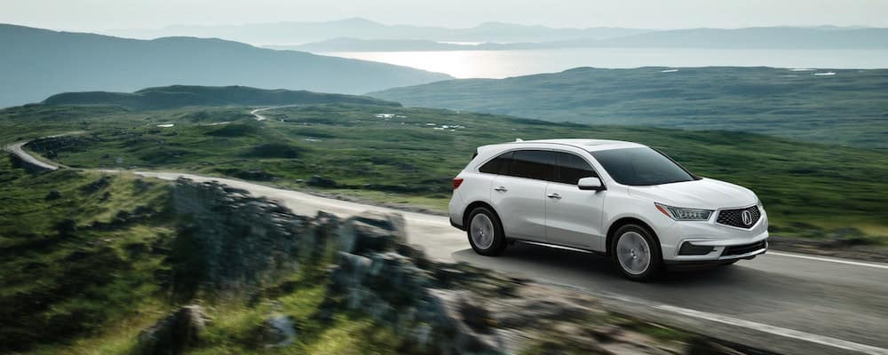 White MDX speeding down a narrow road with green mountains in the background