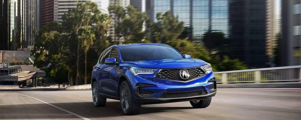 Bright Blue Acura RDX driving down a street with trees in the background