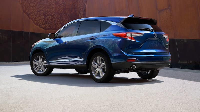 Blue Acura RDX parked in front of a brown wall