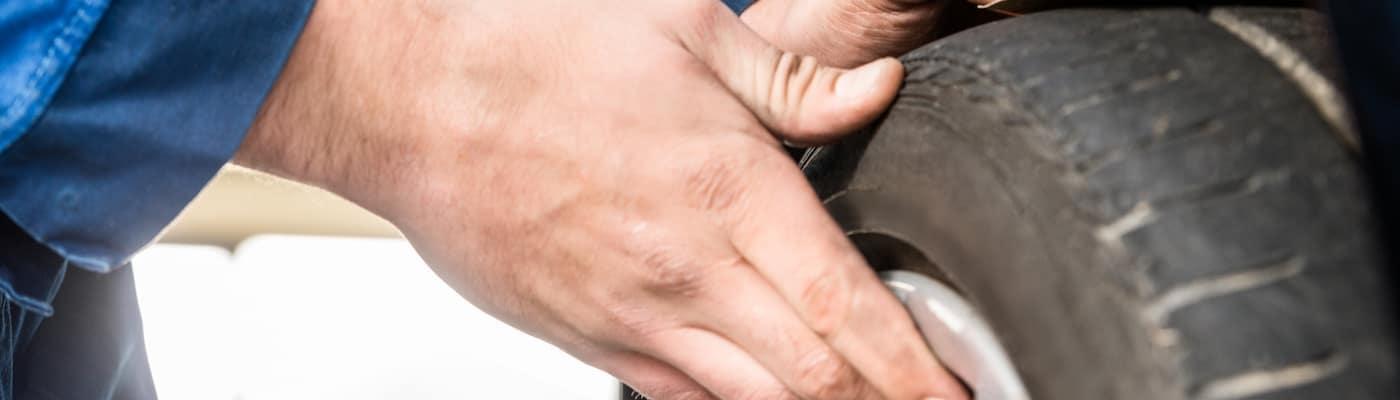 Man Measuring Tire Tread