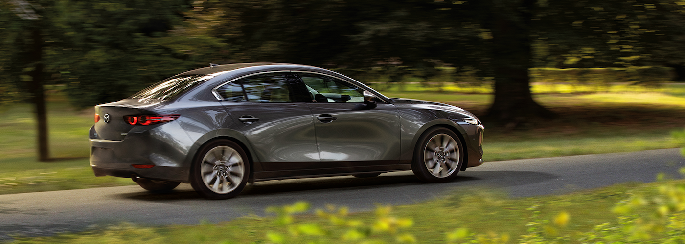 2019 mazda3 gray driving down road with trees