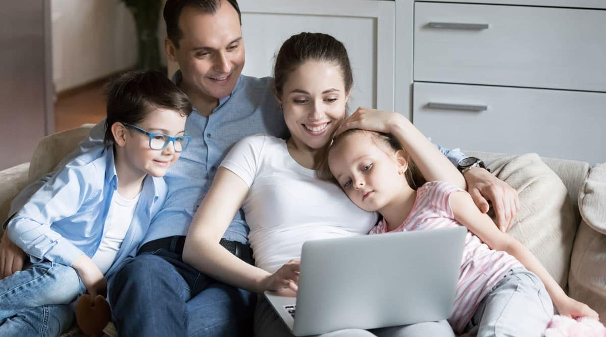 A family gathered up on a couch looking at a laptop screen