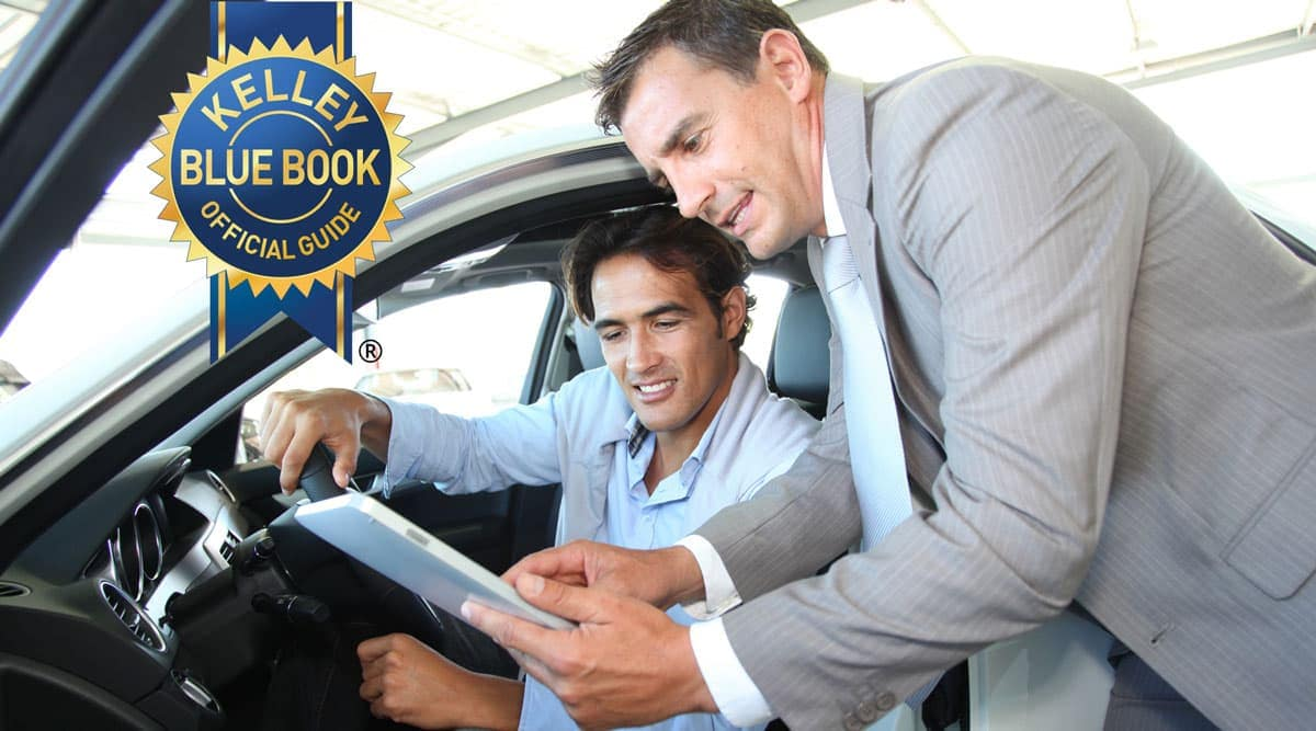 Kelley Blue Book Icon on top of two men next to a vehicle looking at paperwork