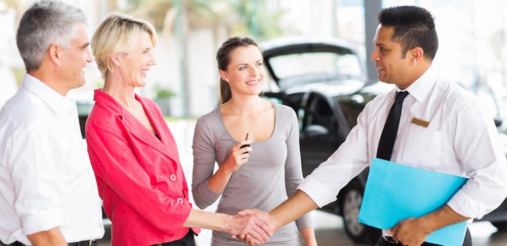 Woman buying or leasing a new car and shaking the hand of the salesman while her husband and daughter show support