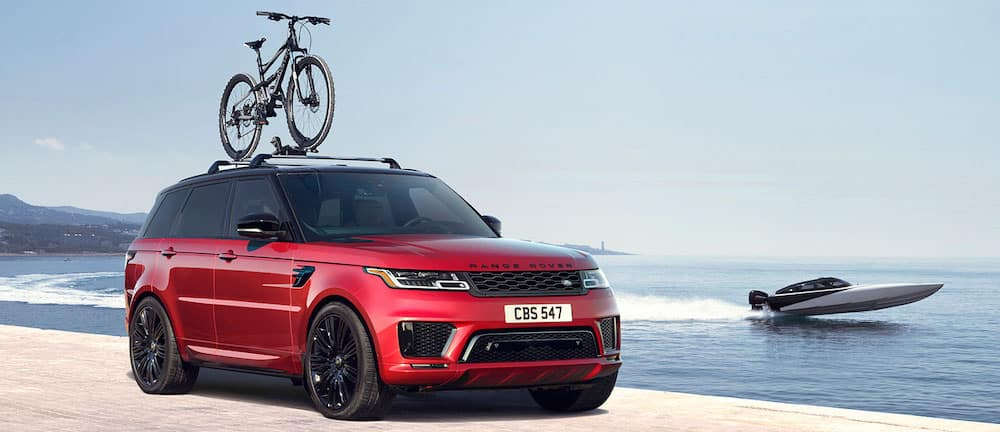 red 2019 range rover sport parked on beach with bicycle mounted on roof