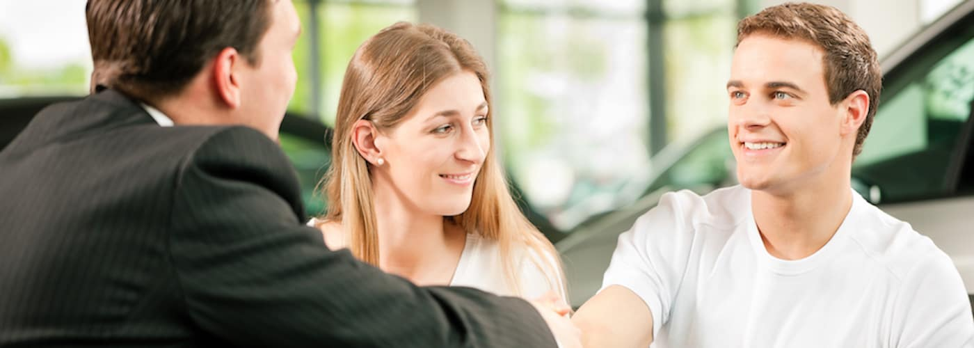 Young Couple at Dealership Shaking Associate's Hand