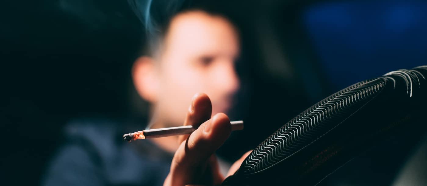 Person Smoking Cigarette in Car