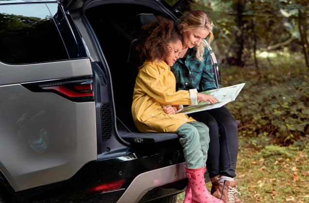 Woman and child sitting on Land Rover Discovery tailgate.