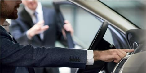 IMAGE FEATURES GENTLEMEN SITTING IN A VEHICLE AND CHATTING WITH A SALES GUIDE.