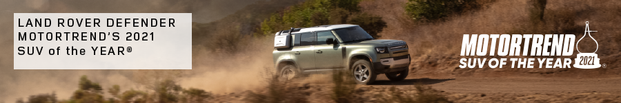LAND ROVER DEFENDER MOTORTREND'S 2021 SUV OF THE YEAR®. SILVER LAND ROVER DEFENDER DRIVING IN MOUNTAIN RANGE.